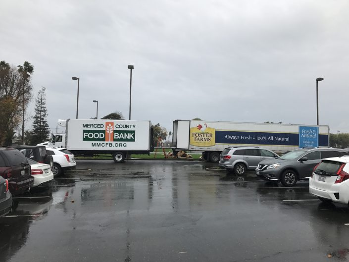 Food bank truck and Foster Farms truck in parking lot