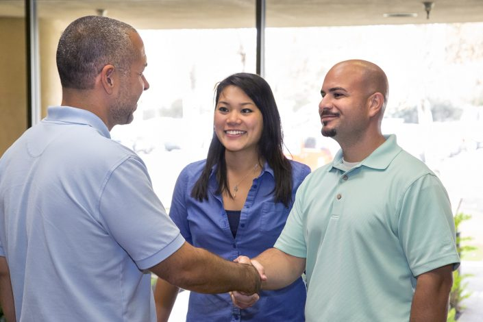 Two men shaking hands and a smiling woman