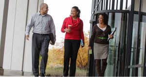 Three Allstate employees of diverse ethnicities walking together.