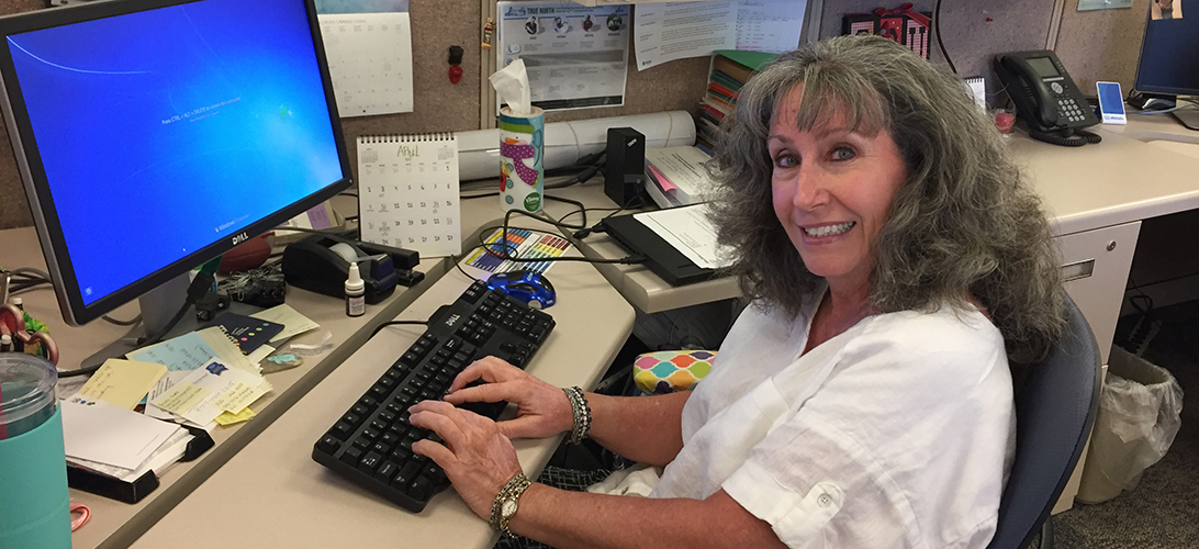Smiling female Allstate employee working at her desk. Click to learn how Donna helps make sure we're always getting better!