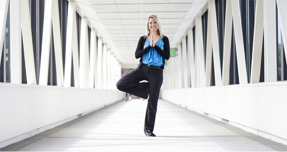 Female Allstate employee standing on one leg in a yoga pose.