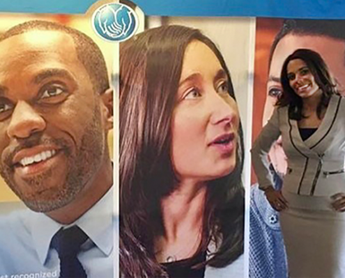 Smiling Allstate employee standing in front of pictures of diverse faces.
