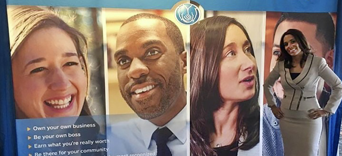 Smiling Allstate employee standing in front of pictures of diverse faces