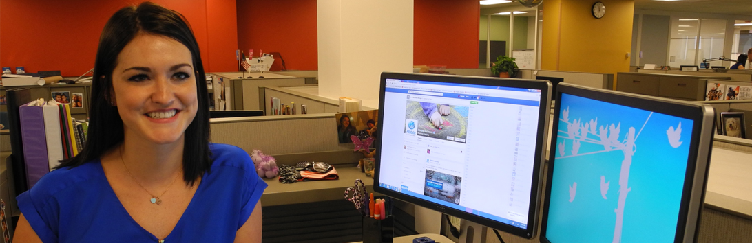 Female Allstate Marketing professional at her desk, working on social media.