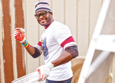 Smiling, male Allstate employee holding a paintbrush in front of a half-painted wall.