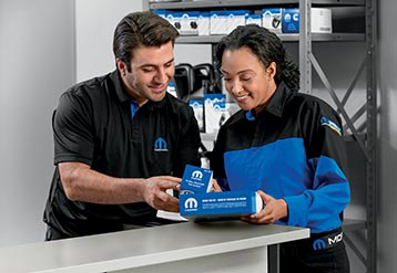 Two employees look at Mopar® aftermarket parts.