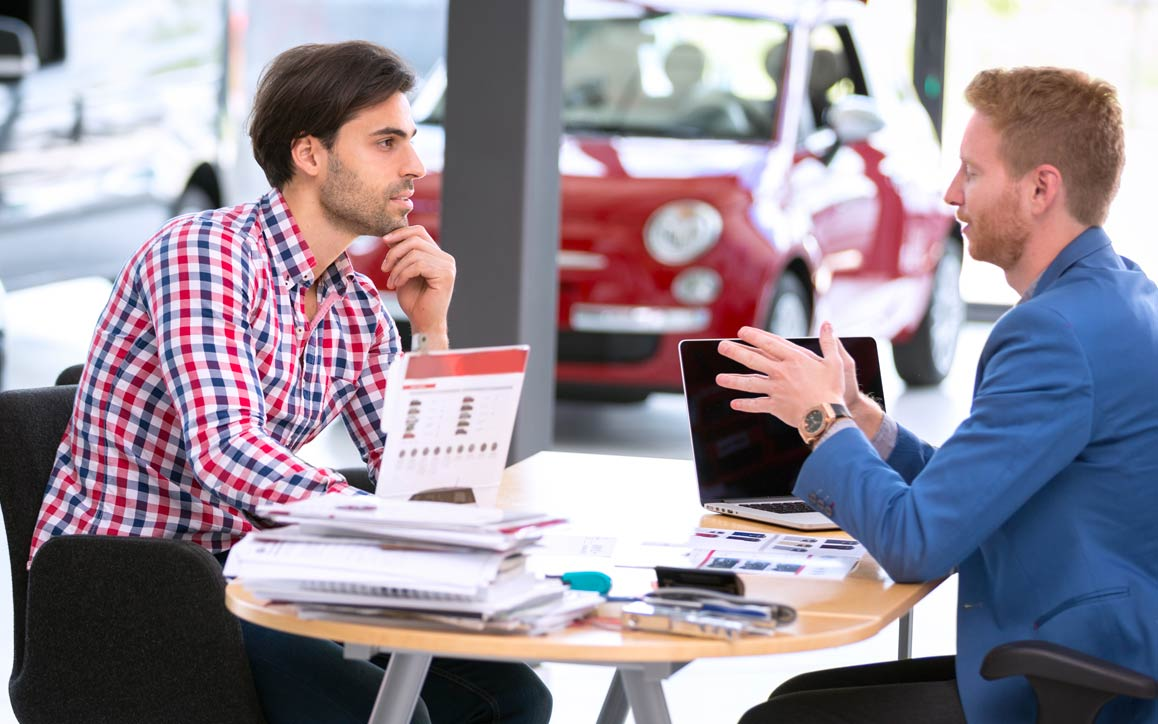 Employee and customer in automotive showroom