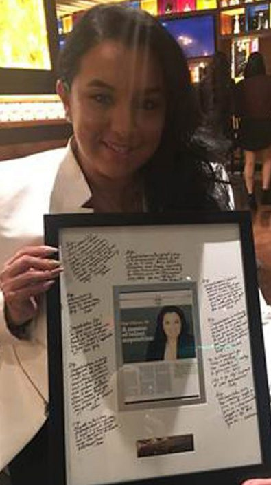 Award-winning ADP associate holds a photo in a frame, with encouraging words written on the mat around the photo