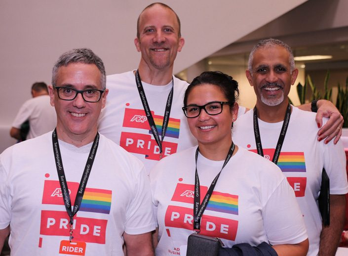 Four ADP associates wearing Pride t-shirts pose for a photo before the cycling event.