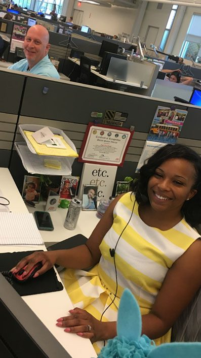In the foreground, Keya, an ADP Tech Support Analyst and U.S. Army Veteran, is seated in a cubicle. In the background, her colleague, Rob, is seated in the cubicle next to her.