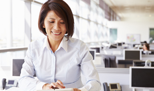 Woman seated in an office environment looking down at her work