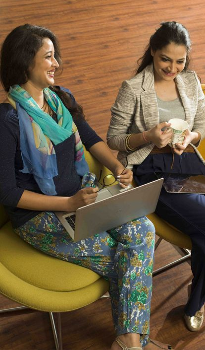 Two women seated next to each other collaborating on ideas