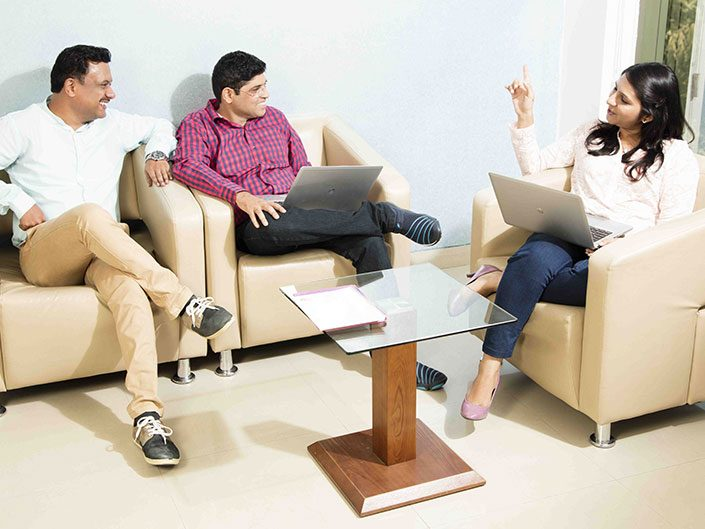 Two men and a woman casually seated and discussing a project
