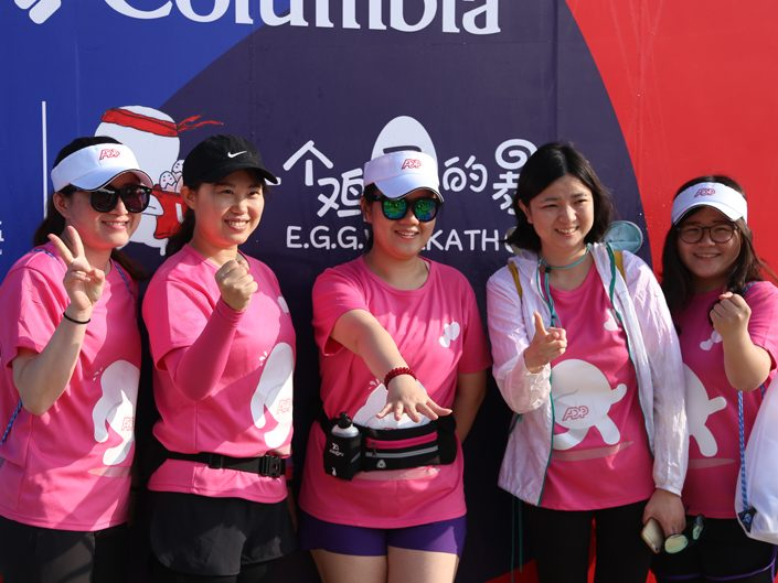 5 female ADP employees posing for a picture in pink Egg Walk T-shirts.