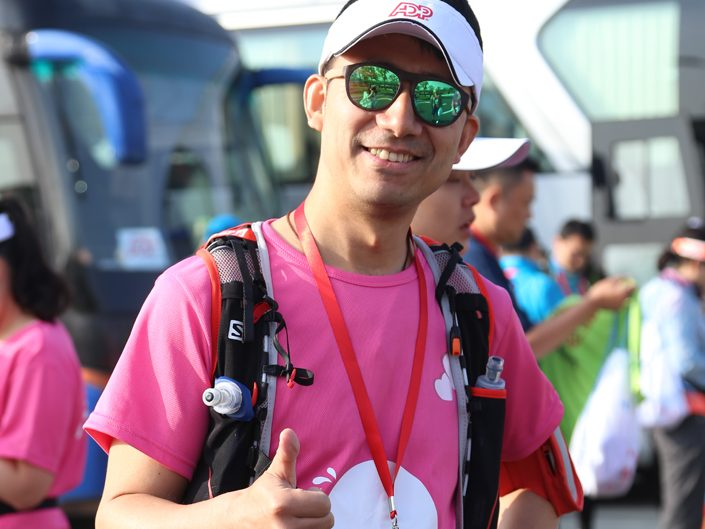 1 male ADP employee in sunglasses and pink Egg Walk T-shirt giving thumbs-up sign