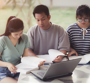 Three students seated together around a laptop working on a project together