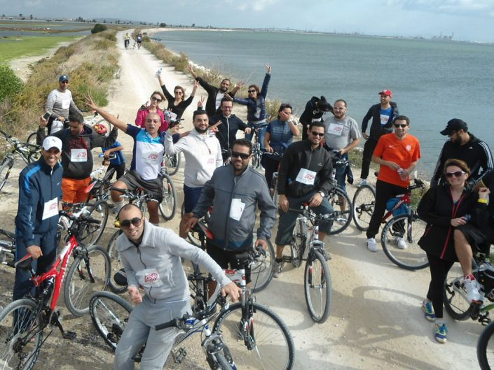 Team of ADP cyclists waving and smiling along the Tunisian coastline.