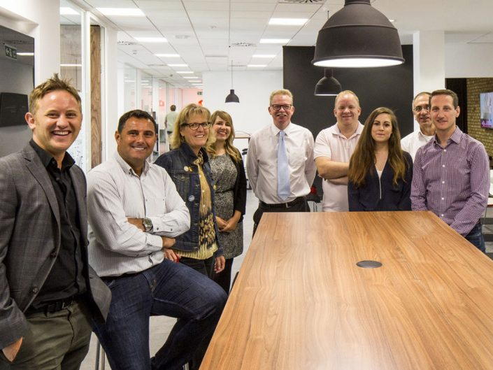 Team of smiling ADP associates in the UK standing around a conference table