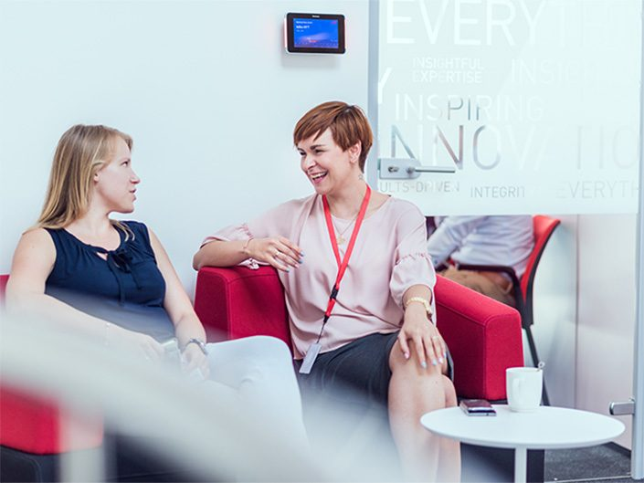 Two women sit in comfortable chairs in an ADP workspace, taking and smiling.