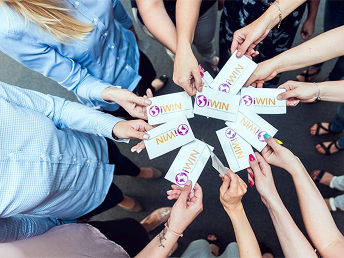 The hands of eleven female ADP associates form a circle. Their hands are holding cards emblazoned with the logo of the International Women's Inclusion Network.