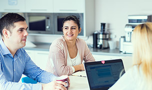 One man and two women sit at a table in an associate break room. One woman is looking at an open laptop, while the man holds a cup of coffee. There are microwaves and a coffee maker in the background.