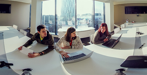 Two women and one man sit at a long curved counter, in a shared workspace, in front of a large window looking out over the city. The women are working on their laptops, while the man holds a piece of paper and glances over at one of the laptop screens.