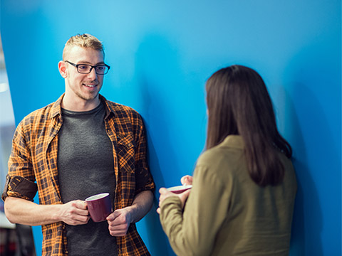 A man and woman have a casual chat in the hallway over a cup of coffee.