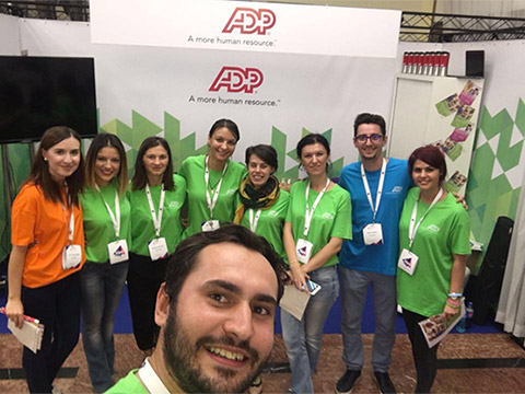 Nine ADP associates pose for a photo, with one man very close up in the foreground.