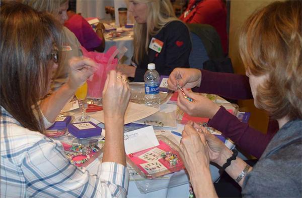 """Goście wydarzenia ADP """"Kobiety w przywództwie"""" siedzą razem przy okrągłym stole i wykonują zadanie grupowe."""