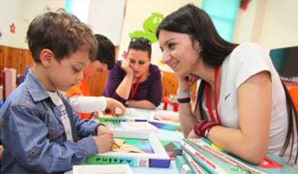 Dwie wolontariuszki siedzą przy stole, pomagając dwóm chłopcom w czytaniu i innych zajęciach edukacyjnych.