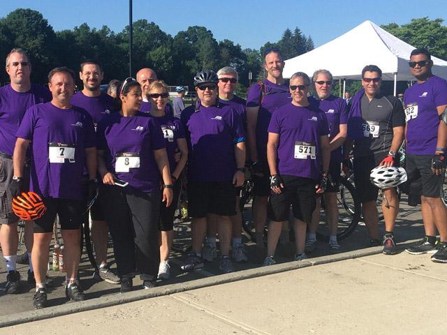 Grupa pracowników ADP noszących fioletowe podkoszulki i strój rowerowy, którzy wzięli udział w wyścigu Pedal for Preservation w stanie New Jersey.
