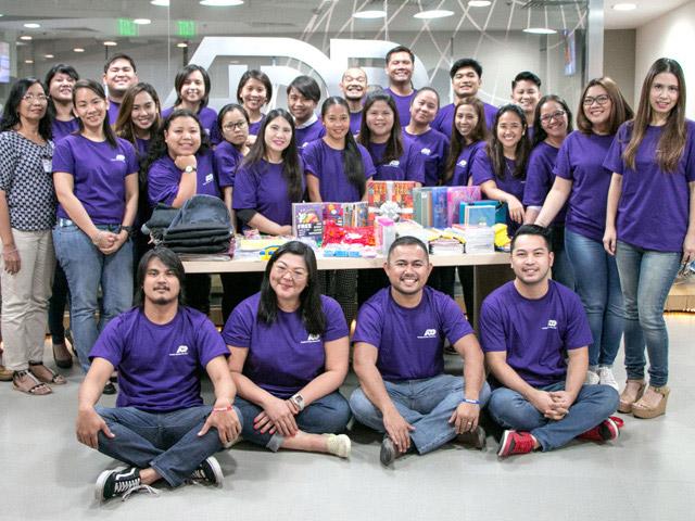Grupa pracowników ADP noszących fioletowe podkoszulki, którzy wzięli udział w programie Back to School na Filipinach.