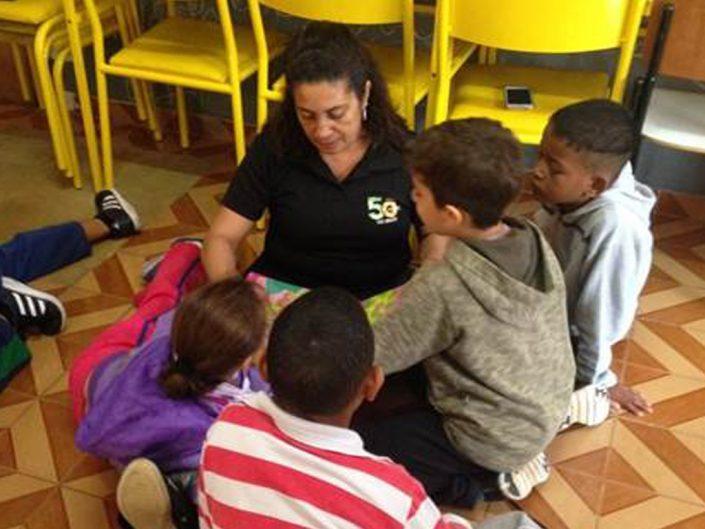 Pracownik ADP, który zgłosił się do programu Read to Children w Brazylii, czytający czworgu otaczających go dzieci.