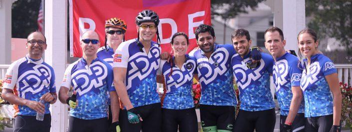 Zespół pracowników ADP w stroju rowerowym, ośmioro mężczyzn i jedna kobieta.