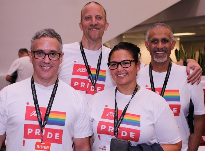 Czterech pracowników ADP w podkoszulkach Pride pozuje do zdjęcia przed wyścigiem rowerowym.