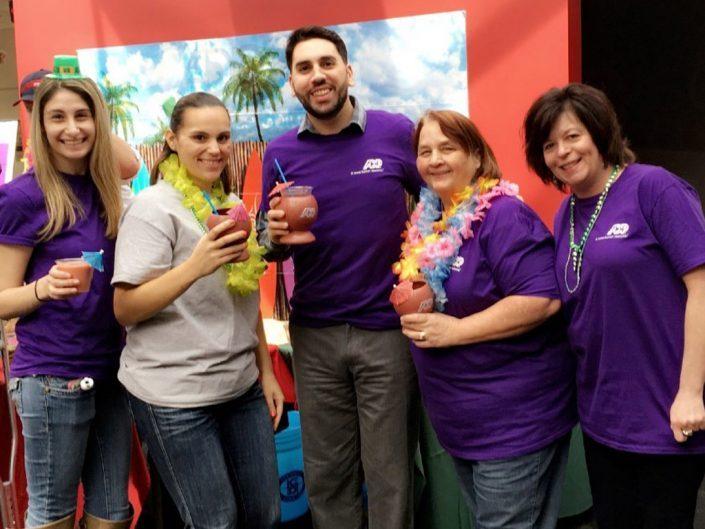 Pięciu pracowników ADP pozuje do zdjęcia grupowego podczas hawajskiego wydarzenia tematycznego. Czworo z nich trzyma tropikalne drinki, dwoje nosi również wieńce lei na szyjach.