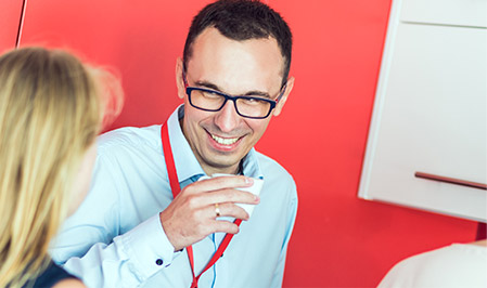 A man wearing glasses laughs with a woman, while sitting in a brightly painted work area.