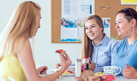 Three women sit together in a break room, enjoying a casual conversation over lunch.