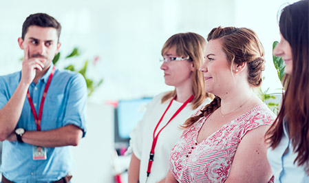 Three women and one man stand during a meeting of entry-level sales professionals.