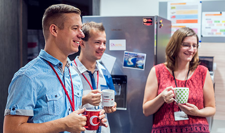 Two male associates and one female have a stand up meeting in an ADP breakroom, as they enjoy hot beverages in ceramic coffee mugs.