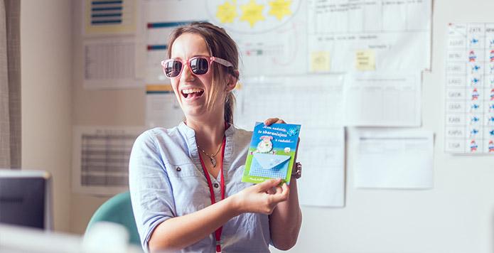 Kobieta w okularach przeciwsłonecznych prezentuje małą, jaskrawo zapakowaną paczkę. Ściana za jej plecami jest wypełniona wykresami, arkuszami kalkulacyjnymi i innymi danymi.
