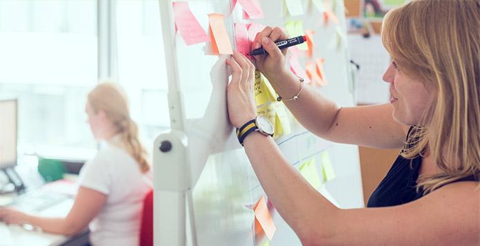 Kobieta dokłada notatkę do tablicy, na której umieszczonych jest już wiele innych notatek. W tle inna kobieta pracuje przy biurku.