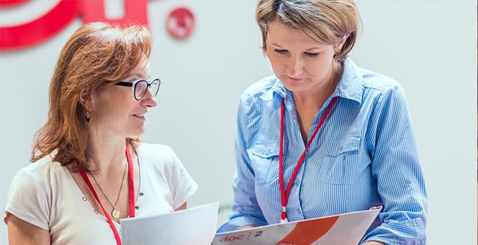 Dwie kobiety stoją w korytarzu, patrząc na dokumenty. Na ścianie za ich plecami widać logo ADP.