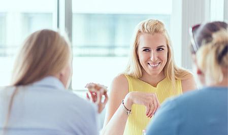 Trzy kobiety siedzą w biurze ADP. Dwie są zwrócone plecami do obiektywu, zaś trzecia szeroko się uśmiecha.