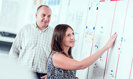 Mężczyzna i kobieta stoją przed ścianą pełną wykresów i innych informacji. Kobieta wskazuje konkretny zbiór punktów danych.