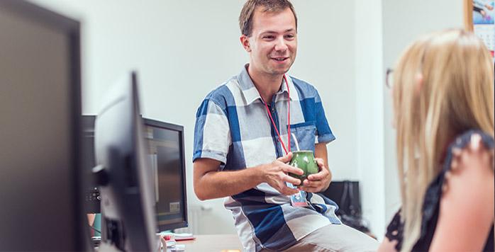 Mężczyzna siedzi przy stole we wspólnym miejscu pracy, pije gorący napój i rozmawia z koleżanką z pracy siedzącą obok niego.