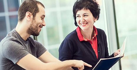 Un bărbat și o femeie stau unul lângă celălalt. Femeia ține un caiet deschis, în timp ce el arată spre o pagină anume.