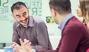 Un bărbat râde entuziasmat în timp ce vorbește cu un alt bărbat ce stă cu spatele la cameră. Pe fundal apare și o femeie. Toți sunt într-o cameră de ședințe ADP cu un design modern.