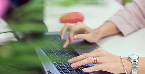 Imagine de aproape cu mâinile unei femei care tastează la laptop. La mâna stângă aceasta poartă un ceas, un inel și o brățară.