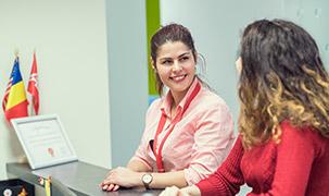Două femei stau la ghișeu într-un birou de resurse umane la ADP în care este prezent steagul României.
